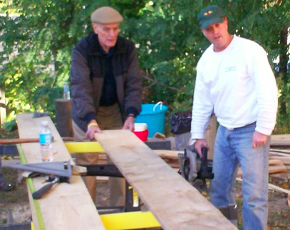 "Andy Clark (right) with his dad Jim Clark working on one of the 1x12"" rough-cut hemlock boards used to restore the original ""board and batten"" siding for the barn."