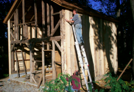 Volunteers Andy Clark (on ladder) and Fred Swartz work on the May Barn restoration in October.